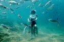 """سيدة تتظاهر بقيادة دراجة خلال الغوص تحت الماء بمدينة """"بولا"""" في كرواتيا"""