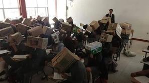 معلم يغطي رؤوس الطلاب بصناديق كرتونية لمنعهم من الغش!