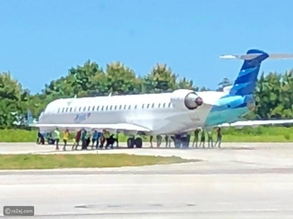 موظفو مطار إندونيسي يقومون بدفع طائرة ركاب على طول المدرج!